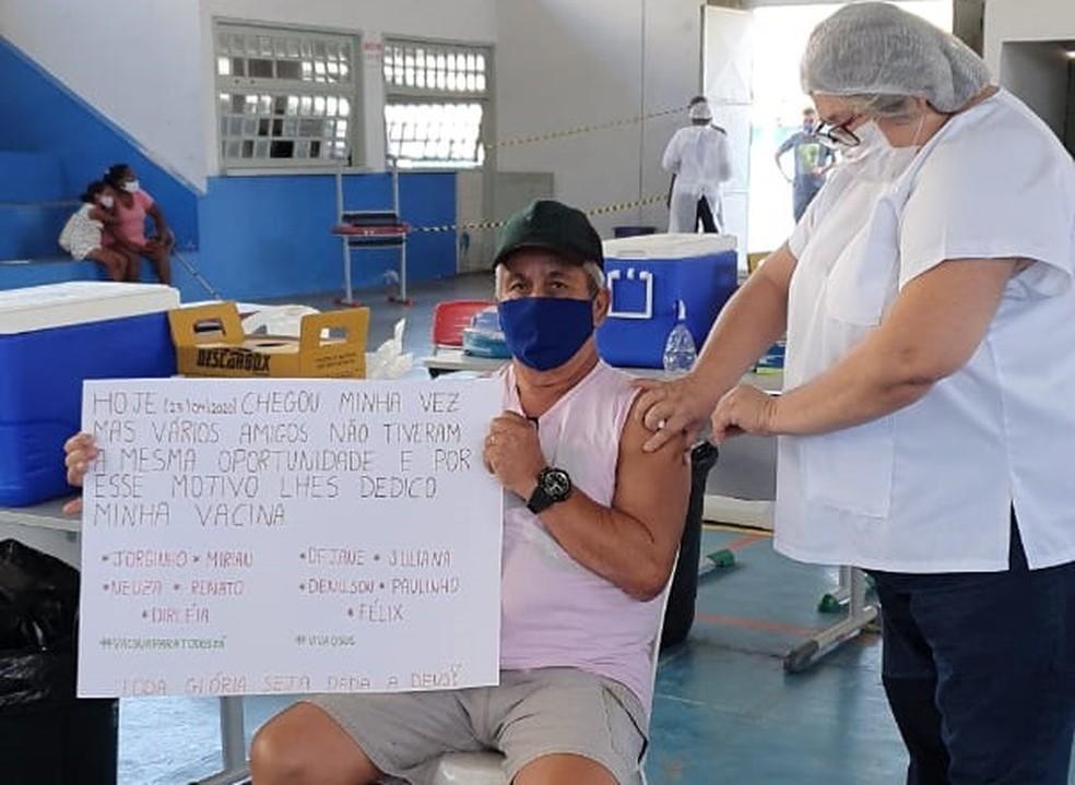 Idoso se vacina segurando cartaz com nomes de amigos vítimas da Covid-19